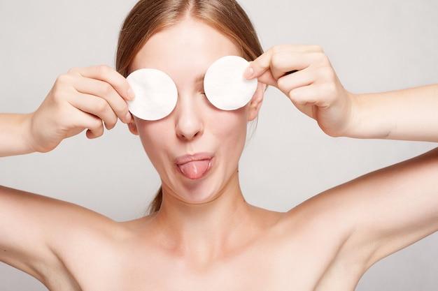 Donna felice che si pulisce il viso con dei dischetti di cotone