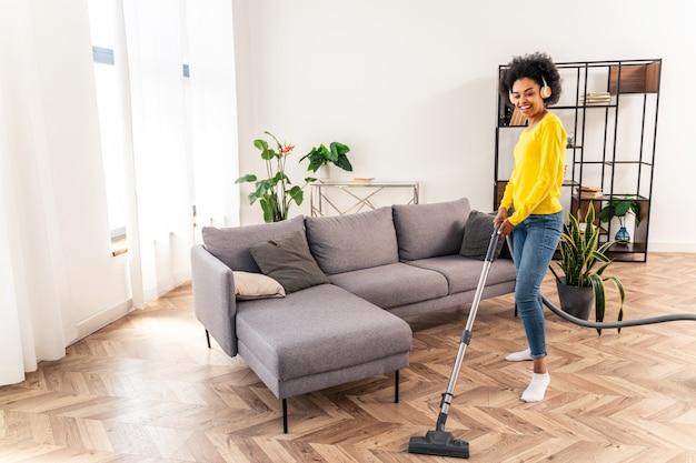 Donna felice che pulisce casa con l'aspirapolvere e ascolta musica