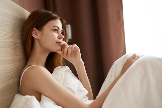 Donna felice sotto le coperte nel letto vicino alla finestra al mattino aspetto sognante modello