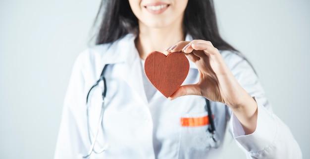 Cuore rosso della mano felice del medico della donna