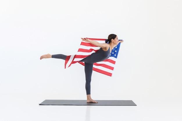 Donna felice che fa yoga in piedi su una gamba sola su un tappetino su sfondo bianco con bandiera americana