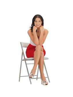 Donna felice in abito su una sedia
