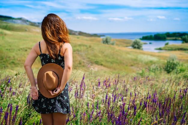 Una donna felice in abito tiene un cappello con sfondo di fiori di campo in fiore ed erba nella zona collinare