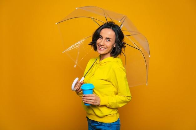 Donna felice vestita con una felpa gialla, sotto un ombrello trasparente, con una tazza blu nella mano sinistra, in piedi di lato.