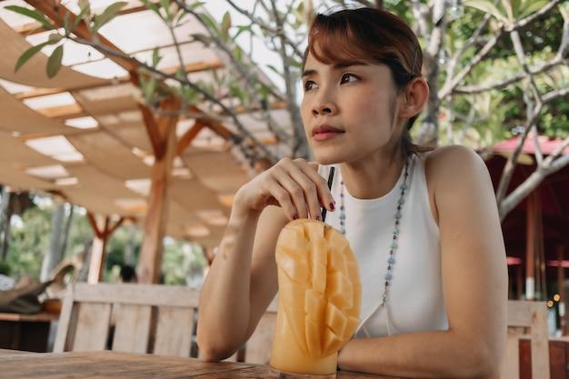 Una donna felice beve un frullato di succo di mango in una giornata estiva