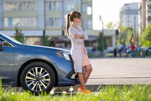 Autista donna felice in abito casual che si gode una giornata calda vicino alla sua auto in una strada estiva