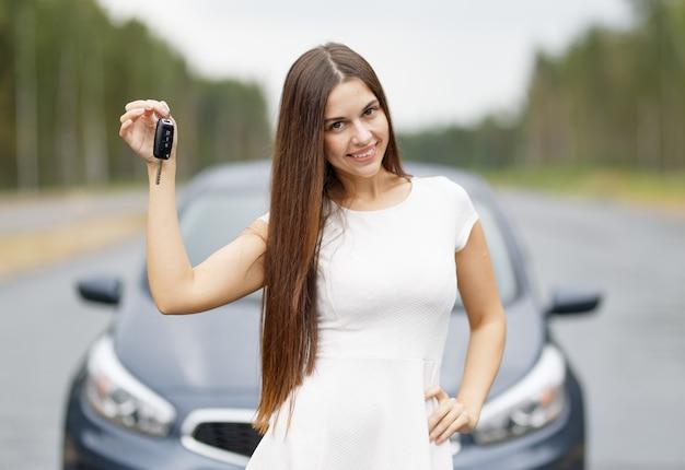 Driver della donna felice che mostra le chiavi della macchina all'aperto
