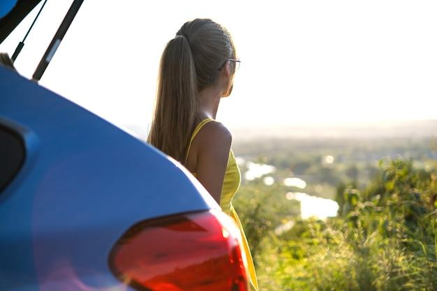 Autista donna felice in abito estivo godendo serata calda vicino alla sua auto. concetto di viaggio e vacanza.