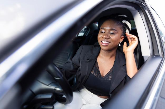 Donna felice alla guida della sua auto personale