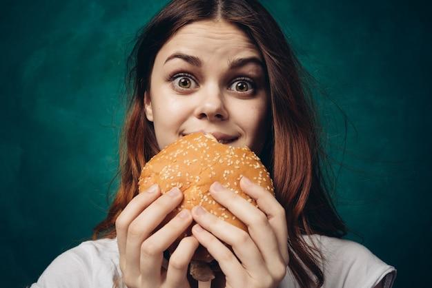 Donna felice che mangia un hamburger