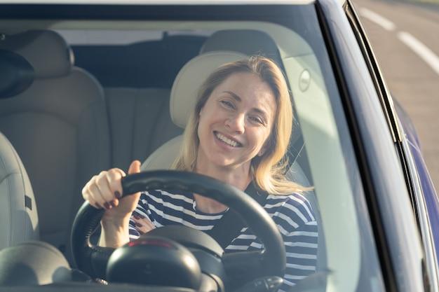 La donna felice si diverte a guidare l'auto nuova eccitata autista femminile in allegria automobilistica durante le vacanze in viaggio