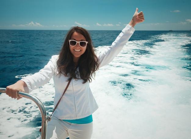 Donna felice che gode di una soleggiata giornata estiva su una barca