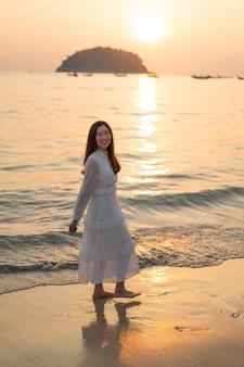 Donna felice che va viaggiare sulla spiaggia di sabbia tropicale in estate