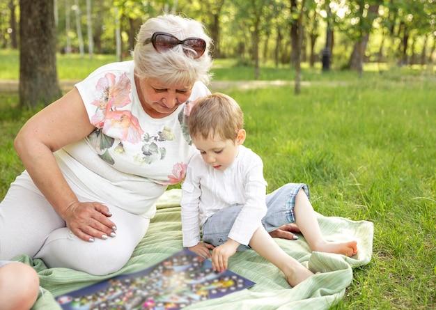 Donna felice e nipote che giocano insieme gioco da tavolo nel parco