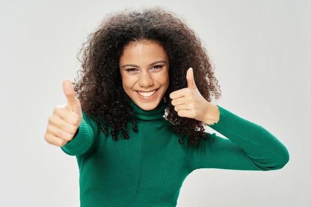 Una donna felice in un maglione verde sorride alla telecamera