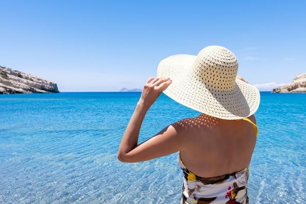 Donna felice in un cappello su una spiaggia tropicale