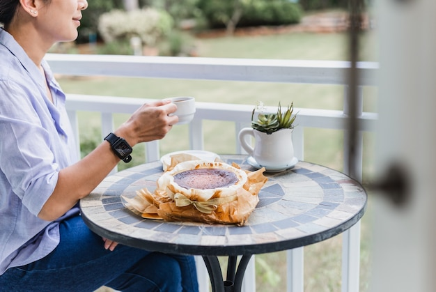 Donna felice che mangia caffè e torta speciale sulla celebrazione della quarantena del tavolo a casa.
