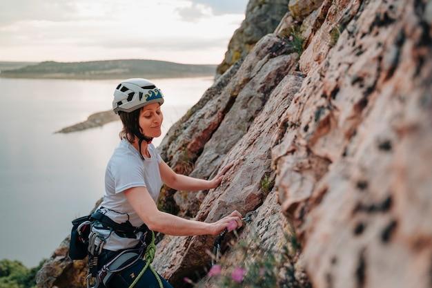 Donna felice sulla trentina che scala una montagna al tramonto