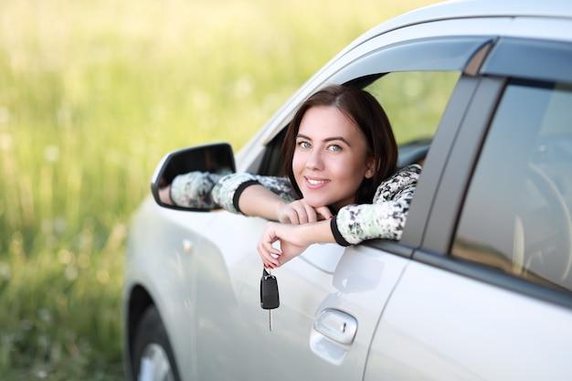 Donna felice nella sua macchina che tiene le chiavi
