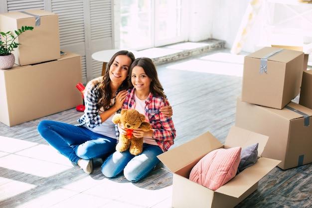 Una donna felice e la sua graziosa figlia stanno disimballando scatole di cartone sedute sul pavimento dopo il trasferimento