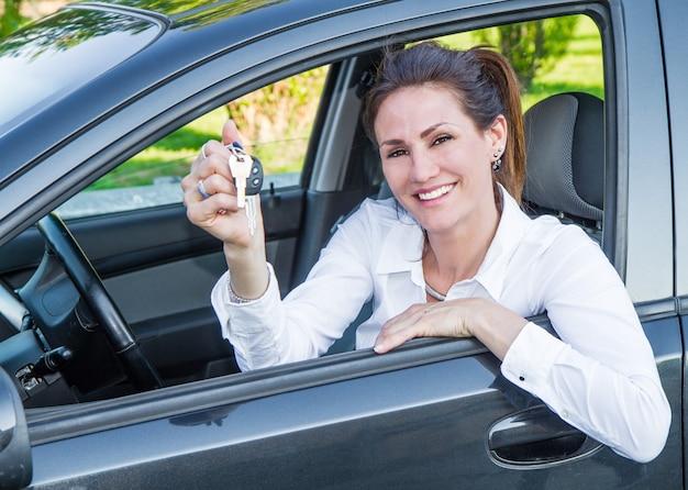 Donna felice nella sua nuova macchina