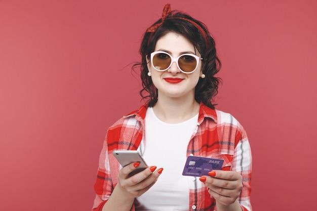 Carta di credito della stretta della donna felice. sfondo rosa isolato.