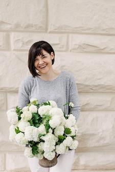 Donna felice che tiene un secchio con fiori di ortensie