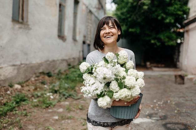 Donna felice che tiene un secchio con fiori bianchi stagionali