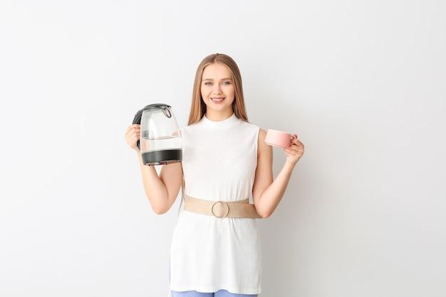 Donna felice che tiene bollitore elettrico e tazza su sfondo bianco