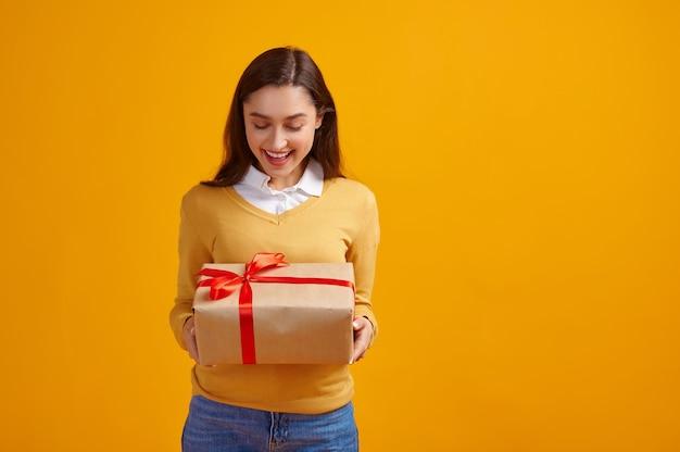 Felice donna azienda confezione regalo con nastri rossi, sfondo giallo. la bella persona femminile ha ricevuto una sorpresa, un evento o una festa di compleanno