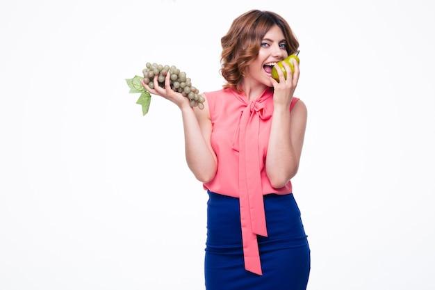 Donna felice che tiene l'uva e mangia la pera