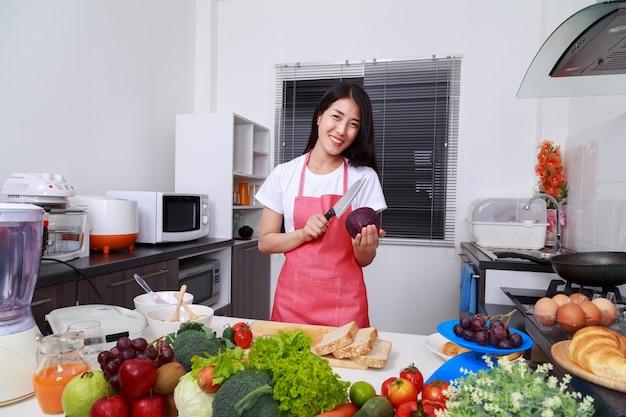 Donna felice che tiene cavolo e coltello viola nella stanza della cucina
