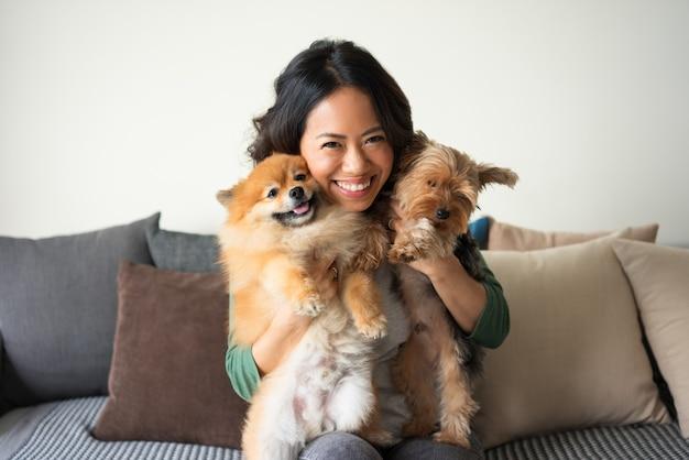 Donna felice che tiene yorkie e spitz cani sul divano