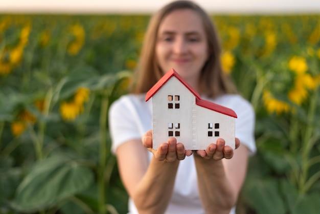 La donna felice tiene sulle sue palme il modello della casa. case ecologiche. serre.