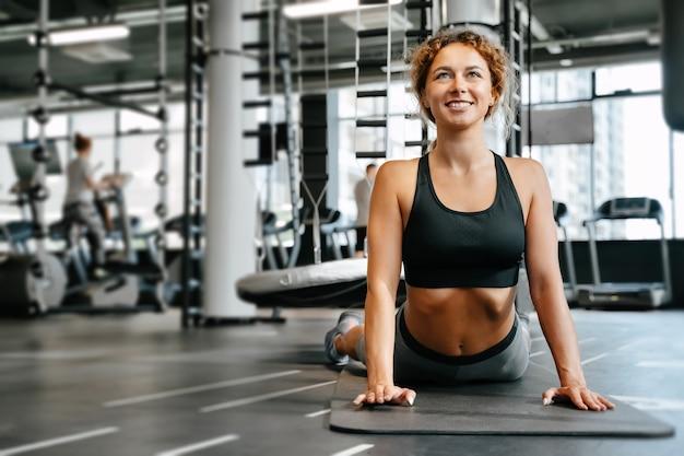 La donna felice sta facendo stretching yoga sul pavimento sdraiato sullo sfondo sfocato del concetto di palestra di ...