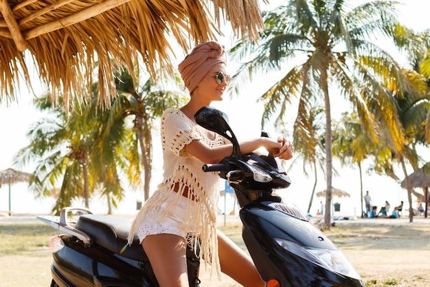 La donna felice sta guidando uno scooter sulla spiaggia tropicale con palme
