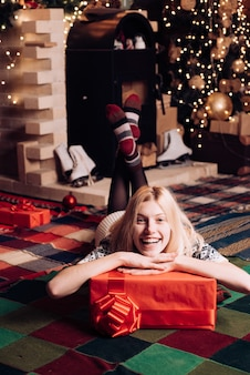 La donna felice è sdraiata sul pavimento con un regalo. periodo natalizio. ragazza bionda molto bella sopra l'albero di natale.