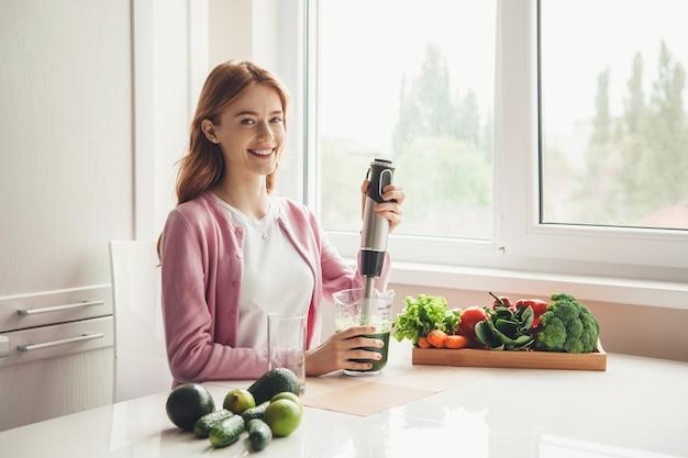 La donna felice sta facendo il succo di verdura fresca utilizzando uno spremiagrumi sorridente
