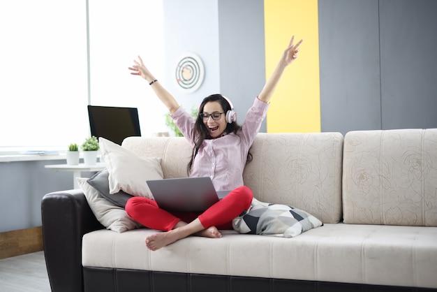 La donna felice è seduta sul divano che indossa le cuffie con gioia alzando le mani