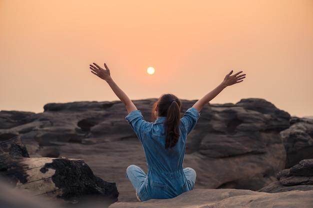 Donna felice in camicia di jeans alzando le braccia e guardando il tramonto sul canyon di roccia nel parco nazionale