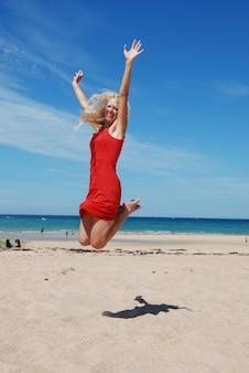 Donna felice che salta sulla spiaggia