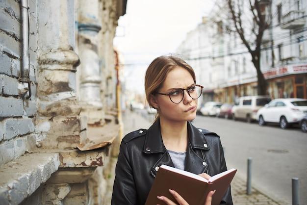 Donna felice in una giacca di pelle con un libro in mano