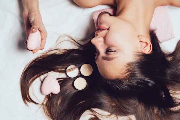 La donna felice si trova su fondo bianco dopo i trattamenti termali