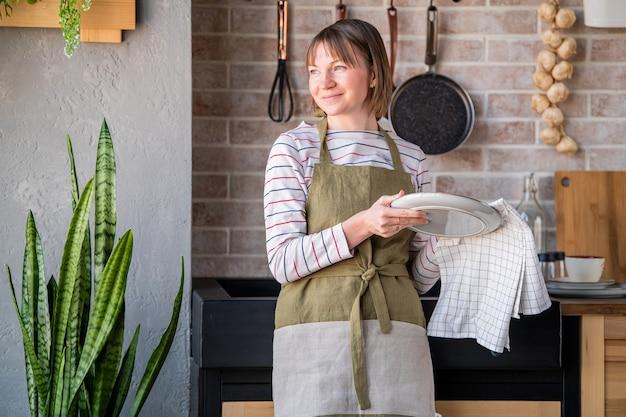 Donna felice in un grembiule di lino in piedi in cucina vicino al lavandino, pulendo un piatto con un asciugamano di lino