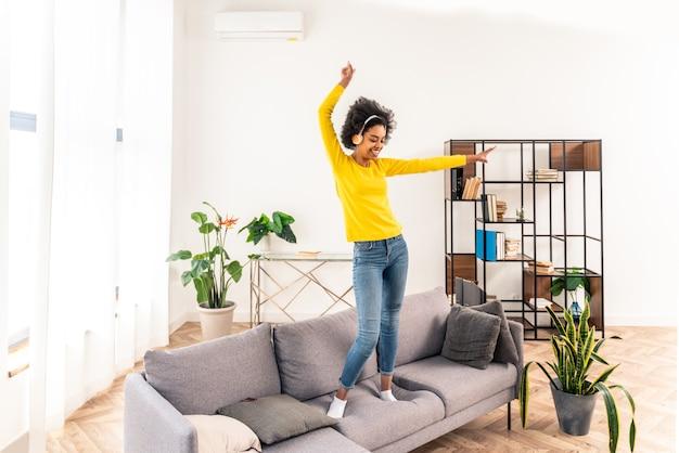 Donna felice che ascolta musica che salta e balla sul divano di casa
