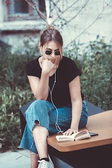 Donna felice che ascolta musica con gli auricolari e legge un libro per strada