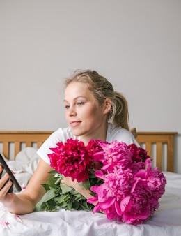 Felice donna sdraiata sul letto con indosso un pigiama, godendosi il bouquet di fiori di tulipano di peonia e usando il telefono