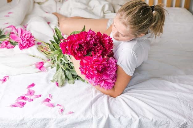 Felice donna sdraiata sul letto in pigiama, godendosi il bouquet di fiori di tulipano di peonia
