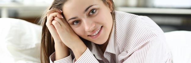 La donna felice in una camicia da uomo si trova sul letto