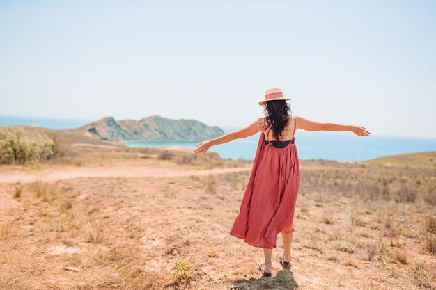 La donna felice all'aperto sul bordo della scogliera gode della vista sulla roccia della cima della montagna